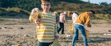Tête de poupée d'apparence de garçon tout en nettoyant la plage photos stock
