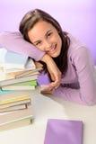 Tête de repos de sourire de fille d'étudiant sur des livres Photographie stock libre de droits