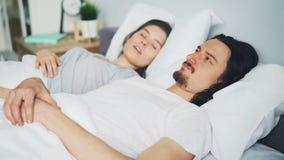 Tête malheureuse de bâche de mari d'homme avec l'oreiller tandis qu'épouse ronflant dans le lit banque de vidéos