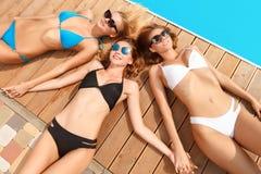 Tête menteuse de trois amies à l'autre à la piscine Photos libres de droits