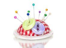 Têtes d'épingle colorées dans la pelote à épingles et le bouton photos stock