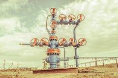 Têtes de puits avec l'armature de valve sur un gisement de pétrole images libres de droits
