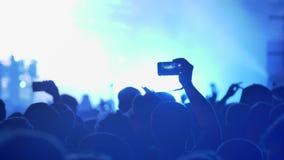 Têtes des personnes au concert de rock, illumination colorée lumineuse banque de vidéos