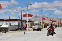 Tíbet, China, junio, 11, 2018 Hombre en paseos de la motocicleta en el camino en el pequeño pueblo de Yakra en el verano fotos de archivo libres de regalías