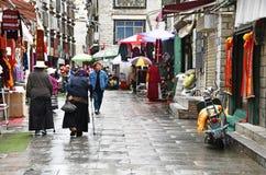 Tíbet, Lasa, China, junio, 03, 2018 La gente que camina en el mesón viejo de Lasa de la ciudad llueve fotos de archivo libres de regalías