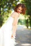 Tímido y sonriendo - la novia mira abajo la tierra mientras que ella presenta Imágenes de archivo libres de regalías