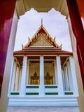 Tímpano com dois quadros de porta dourados na frente do templo tailandês Imagens de Stock