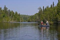 Título de Canoers em um lago woods do norte Fotografia de Stock