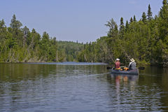 Título de Canoers en un lago woods del norte fotografía de archivo