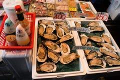 Tóquio de TSUKIJI, Japão - novembro 13,2017: Ostra e molhos frescos, shell do mar, marisco popular de Japão imagem de stock