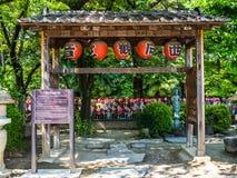 TÓQUIO, JAPÃO - 5 DE AGOSTO DE 2017: Feche acima das lanternas vermelhas que penduram de uma estrutura de madeira, e um Jizo Bodd Imagem de Stock Royalty Free