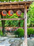 TÓQUIO, JAPÃO - 5 DE AGOSTO DE 2017: Feche acima das lanternas vermelhas que penduram de uma estrutura de madeira, e um Jizo Bodd Foto de Stock Royalty Free