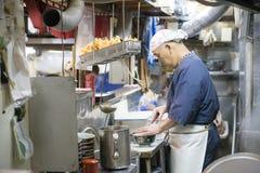 TÓQUIO, JAPÃO - 18 DE FEVEREIRO DE 2016: Os cozinheiros chefe japoneses estão cozinhando dentro Imagem de Stock Royalty Free