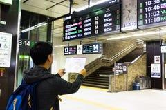 Tóquio, Japão - 11 de maio de 2017: Mapa asiático o do metro da leitura do turista Imagens de Stock Royalty Free