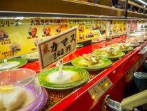 TÓQUIO, JAPÃO -28 JUNHO DE 2017: Feche acima do alimento sortido do japanesse sobre uma tabela, dentro de um sushi da correia tra Foto de Stock