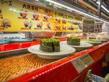 TÓQUIO, JAPÃO -28 JUNHO DE 2017: Feche acima do alimento sortido do japanesse sobre uma tabela, dentro de um sushi da correia tra Imagem de Stock Royalty Free