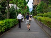 TÓQUIO, JAPÃO O 28 DE JUNHO - 2017: Povos não identificados que andam em um pavimento apedrejado na rua em Shinjuku Gai dourado Foto de Stock