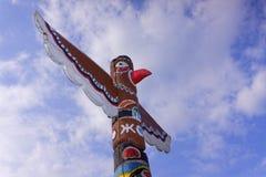Tótem colorido de madera debajo del cielo nublado azul foto de archivo