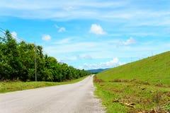 Töm asfaltlandsvägen längs väggen av fördämningen med grönt gräs och blå himmel med moln och berget Arkivfoton