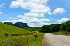 Töm asfaltlandsvägen längs väggen av fördämningen med grönt gräs och blå himmel med moln och berget Arkivbilder