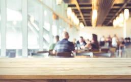 Töm av den wood tabellöverkanten på suddigt av folk i coffee shop Arkivbild