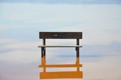 Töm bänkanseendet i mitt av vattnet Arkivbild