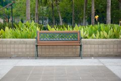 Töm bänken som isoleras i ett offentligt, parkerar med trädgården arkivfoto