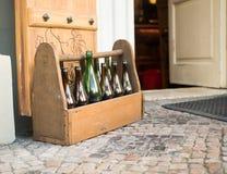 Töm bruna dammiga flaskor i träask på trädgården av restaurangen Royaltyfri Foto
