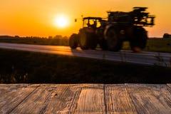 Töm den lantliga wood tabellöverkanten med traktorsilhuette på solnedgångbac Arkivbilder