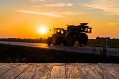 Töm den lantliga wood tabellöverkanten med traktorsilhuette på solnedgångbac Fotografering för Bildbyråer