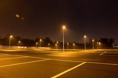Töm den utomhus- parkeringshuset på natten som skins med gatalampor Fotografering för Bildbyråer