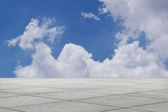 Töm det fyrkantiga tegelplattagolvet boundlessly i blå himmel royaltyfri bild