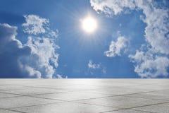 Töm det fyrkantiga tegelplattagolvet boundlessly i blått soligt och himmel arkivfoton