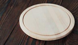 Töm det runda träbrädet för att klippa på en träbakgrund Royaltyfria Foton