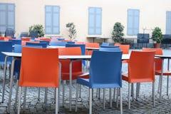 Töm färgade stolar runt om en tabell Arkivfoton