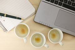 Töm koppar av espresso/kaffe framme av en bärbar dator Arkivfoton