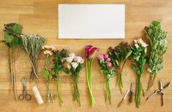Töm pappers- och blommar buketter på vitt trä Royaltyfri Fotografi