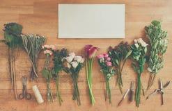 Töm pappers- och blommar buketter på vitt trä Arkivbilder