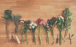 Töm pappers- och blommar buketter på vitt trä Arkivbild