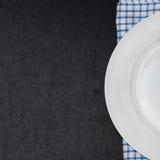 Töm plattan på en servett och svärta bakgrund för din text royaltyfri fotografi