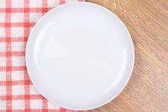 Töm plattan på trätabellen med den rutiga bordduken Royaltyfri Bild