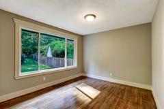 Töm rum med ädelträgolvet och det stora fönstret Royaltyfri Foto