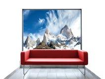 Töm rum med röd soffa- och bergsikt till och med fönster Arkivbild