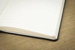 Töm sidor av den öppnade anteckningsboken på trätabellen Arkivfoto