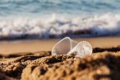 Töm skrynkligt plast- exponeringsglas på kusten arkivfoto