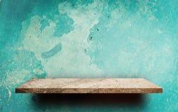 Töm stenhyllan på den Grungy gröna väggen arkivbild