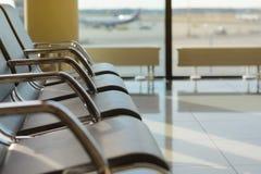 Töm stolar i avvikelsekorridoren på flygplatsen Arkivfoton