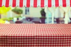 Töm tabellen med den röda kontrollerade bordduken och awing Fotografering för Bildbyråer
