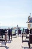 Töm tabeller och stolar framme av restaurangen, ställe till ser Royaltyfri Foto