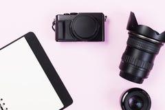 Tömmer den kompakta kameran för tappning med linsutrustning och boken Arkivbild